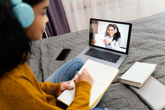 オンライン学校でノートパソコンを使用している10代の少女