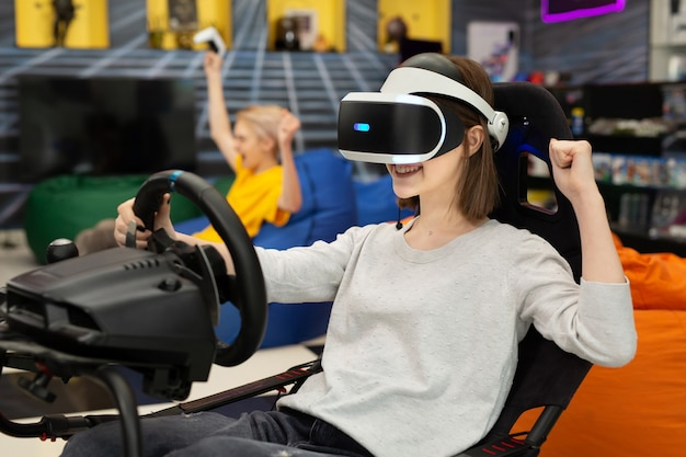 Teenage girl in virtual reality glasses holds the steering wheel and plays a computer game on the console, rejoicing at the victory.