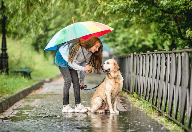 Teenage girl walking with golden retriever dog at rainy day