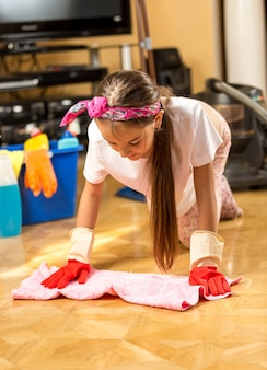 Teenage girl washing wooden floor with cloth at living room