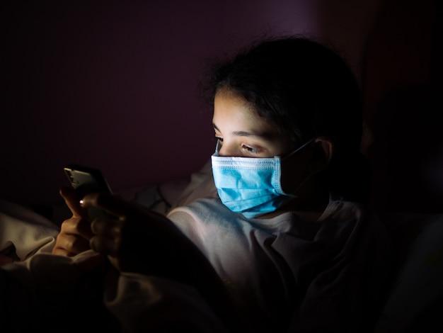 십 대 소녀는 마스크를 착용 하 고 그녀의 휴대 전화, 어두운 사진 확인