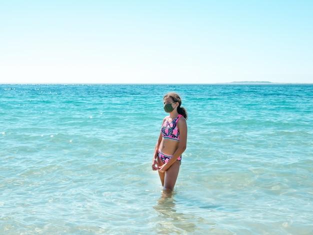 コロナウイルス病を防ぐためにビーチで防護マスクを着ている10代の少女