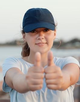 Девочка-подросток в синей бейсболке показывает большие пальцы руки вверх возле моря на закате. выстрел в голову. выборочный фокус. макет кепки