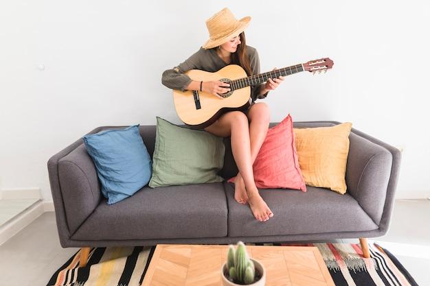 Teenage girl wearing hat playing guitar at home