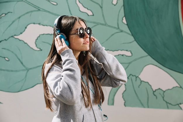 Teenage girl wearing headphones and sunglasses in front of painted wall
