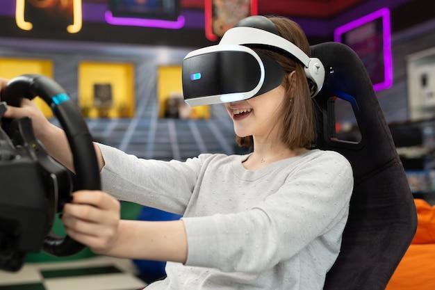 仮想現実の眼鏡をかけた 10 代の少女がハンドルを握り、コンソールでコンピューター ゲームをしている