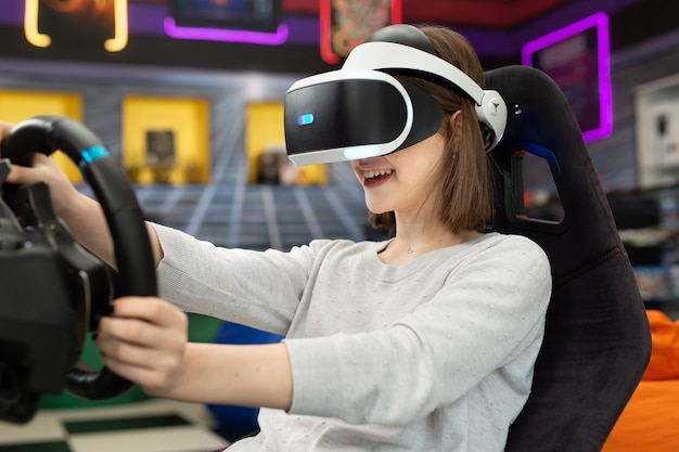 Teenage girl wearing virtual reality glasses, who holds on to the steering wheel and plays a computer game on the console