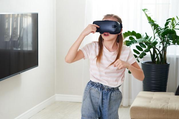 Девочка-подросток нося шлемофон изумлённых взглядов виртуальной реальности и играть, коробку vr.