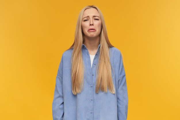 Teenage girl, weeping woman with blond long hair. wearing blue shirt. people and emotion concept. very upset about something, sobbing. watching at the camera, isolated over orange background