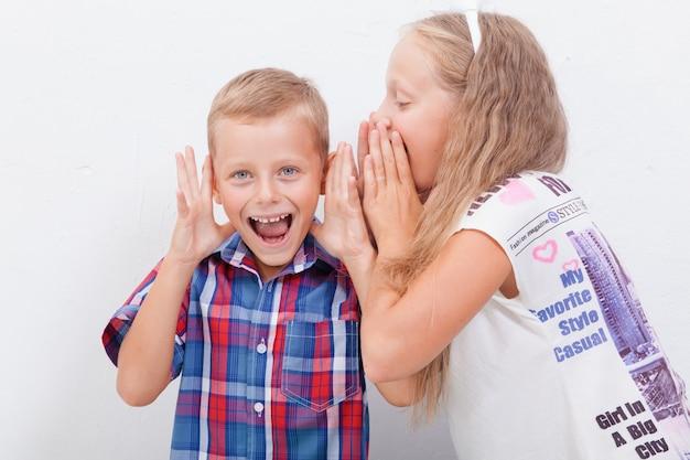 Adolescente che bisbiglia nell'orecchio di un segreto di ragazzi adolescenti su sfondo bianco