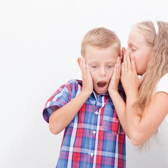 Девочка-подросток шепчет на ухо секретным мальчикам-подросткам на белом фоне