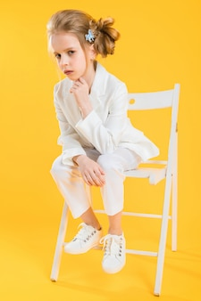 A teenage girl in white clothes is sitting on a chair on yellow