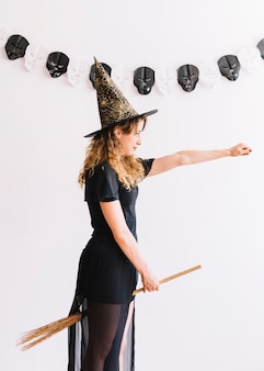 Teenage girl in witch costume with broom