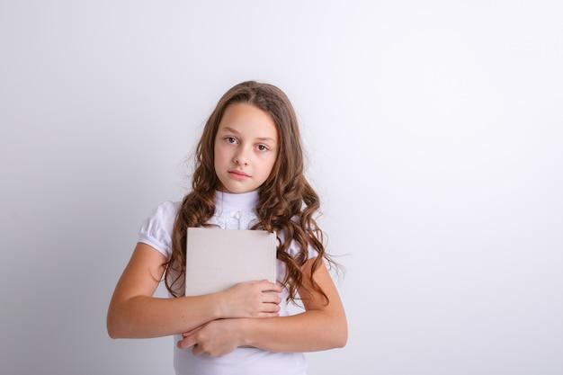 白い背景の上の彼女の手で本を持つ10代の少女。感情の喜び、驚き、悲しみを示しています。