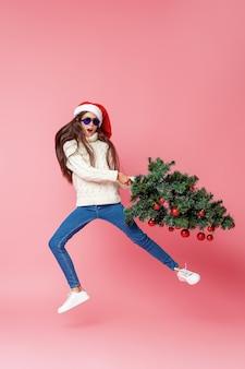 クリスマスツリーを持つ10代の少女