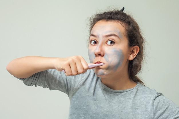 Девушка с косметической маской на лице чистит зубы. маска-скраб для лица.