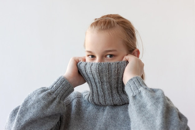 A teenage girl with blonde hair pulled the collar of a gray sweater over her face with her hands, only her eyes are visible.