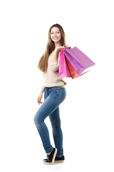 Teenage girl with broad smile holding pink shopping bags