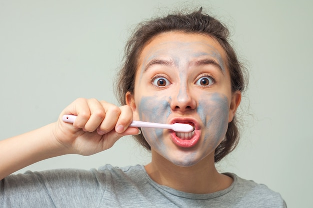 A teenage girl with a cosmetic mask on her face brushes her teeth