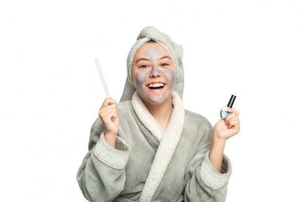 Teenage girl with a cosmetic mask on her face does a manicure. face scrub mask. concept of health and beauty.