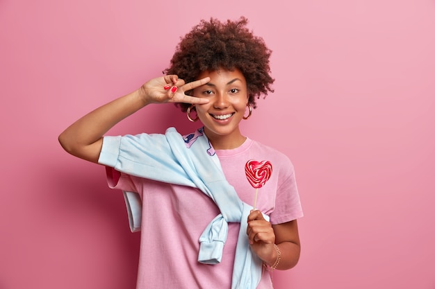 Девушка-подросток с кудрявыми волосами делает победный жест над глазом, имеет счастливое выражение, держит аппетитный леденец на палочке, небрежно одета, позирует