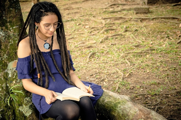 Teenage girl with dreadlocks sitting under the tree and she is reading a book and holding a pencil in her hand. .
