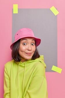 東部の外観を持つ10代の少女は、ピンクの壁に隔離されたカジュアルなパーカーを着て、好奇心旺盛な嬉しい表情で何かを喜んで聞いています