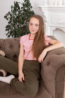 そばかすのある10代の少女がお気に入りの居心地の良いソファに座る