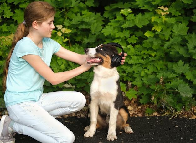 Девочка-подросток с забавной милой австралийской овчаркой трех цветов щенка в наушниках. наслаждайтесь временем, проводимым вместе. слушай музыку. открытый. в летнем парке. уход за домашними животными и дружелюбная концепция.