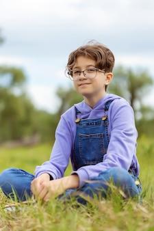 眼鏡をかけた10代の少女は緑の牧草地に座っています