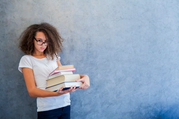 Teenage girl with glasses stands next to the wall and holds several books
