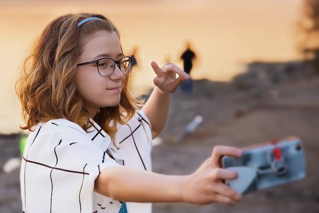 眼鏡をかけた10代の少女が自分撮りをします Premium写真