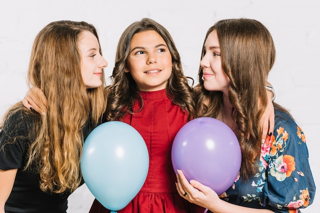 Teenage girl with her two female friends holding balloons in hand