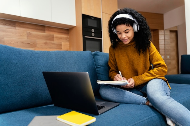 オンライン学校の間にラップトップとヘッドフォンを持つ10代の少女
