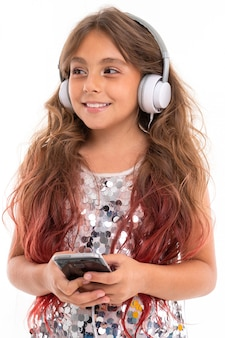 Teenage girl with long blonde hair dyed with tips pink, in shiny light dress, standing with headphones and holding phone in hand