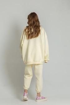 黄色のスポーツ衣装でカメラにポーズをとって長いdarkblond髪の10代の少女