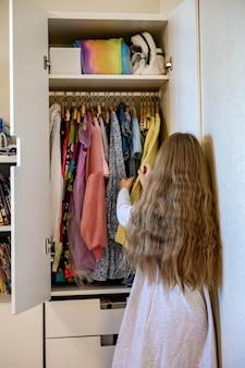 長い髪の10代の少女は、服を丸めて、食器棚にアパレルを置くマリーコンドス法を使用します
