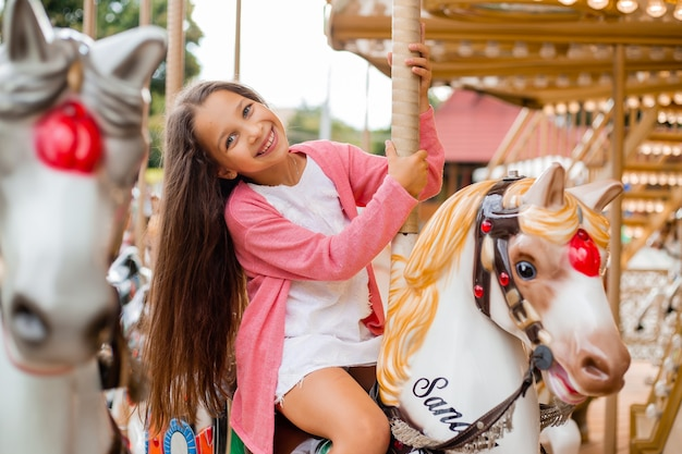 A teenage girl with long hair rolls around on a swing horse carousel. sitting on a horse at an amusement park