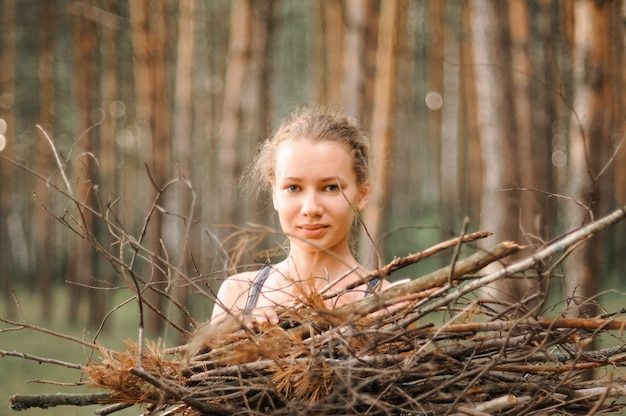 여드름 피부를 가진 10대 소녀는 자연의 여름 숲을 여행하는 동안 모닥불을 위해 나뭇가지 장작을 모읍니다. 젊은 행복한 사람들 생존주의 여행자와 야외에서 현지 여행