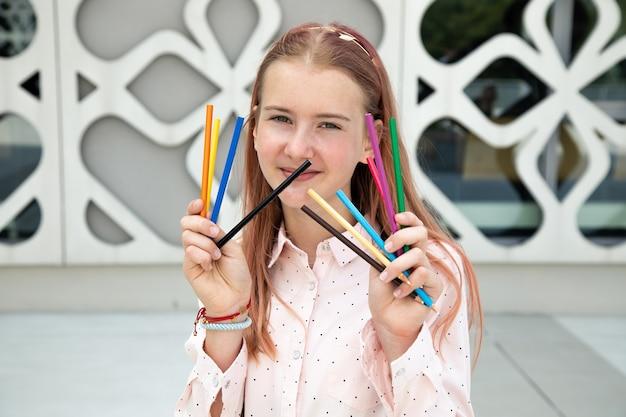 예술 콜라주의 콘크리트 건물 배경에 대해 손에 연필을 들고 있는 분홍색 머리를 가진 10대 소녀