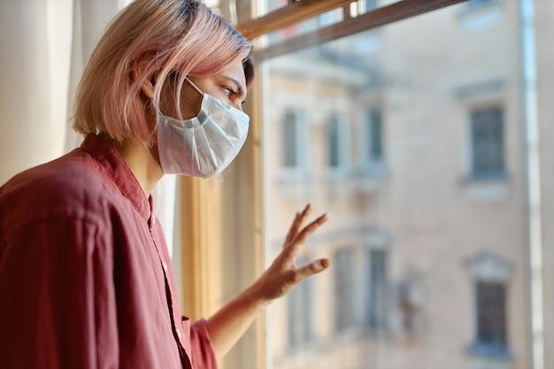 격리 기간 동안 집에 머무는 동안 밖에 서 찾고 유리에 손으로 닫힌 창 앞에 서있는 분홍빛 머리를 가진 십 대 소녀. 코로나 바이러스 전염병 및 사회적 거리두기 개념