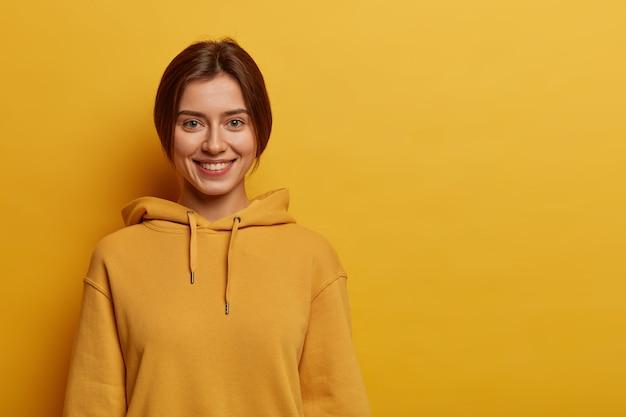 Девушка-подросток с приятной улыбкой, с темными зачесанными волосами, носит толстовку, у нее здоровая кожа, стоит на фоне желтого пространства.