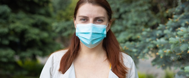 Teenage girl with protective face mask in city park during covid coronavirus pandemic
