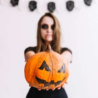 Teenage girl with scary grim and pumpkin in hands