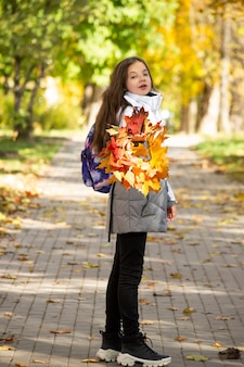 Teenage girl with school backpack stands on sidewalk holding bright wreath of maple leaves