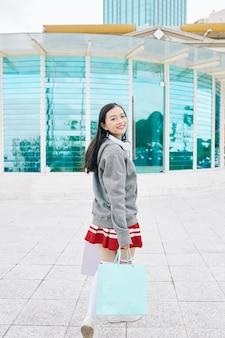 Девочка-подросток с хозяйственными сумками, поворачиваясь назад и улыбаясь в камеру