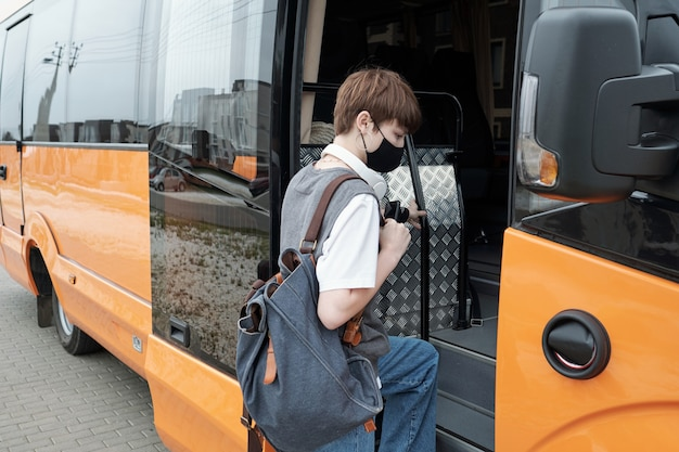 現代のバスに乗っている間サッチェルを保持している顔のマスクを身に着けている短い髪の10代の少女