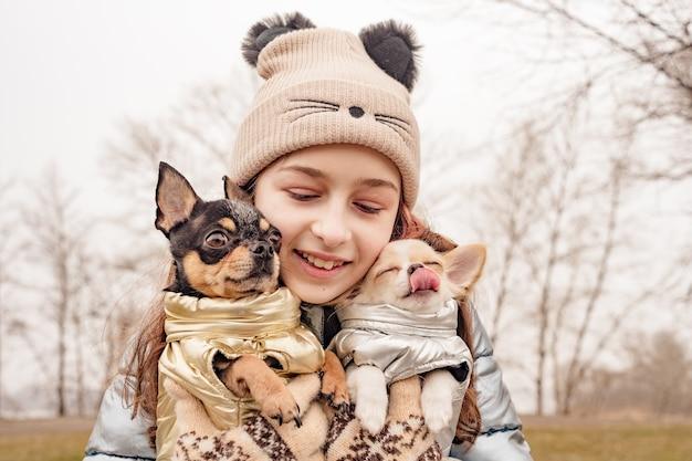 그녀의 팔에 두 치와와 강아지와 십 대 소녀