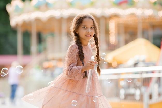 2つのおさげ髪の10代の少女がカルーセルの近くの遊園地で泡を起動し、喜ぶ