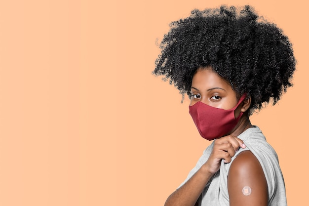 オレンジ色の茶色の背景に分離された彼女の腕にワクチンパッチを持つ10代の少女